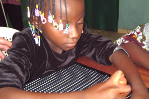 A pupil from the Boulsa Centre for the Blind during a Braille writing class.